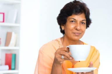 Senior Indian woman drinking green tea