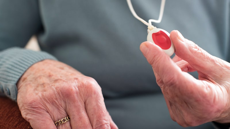 Senior holding a medical alert device
