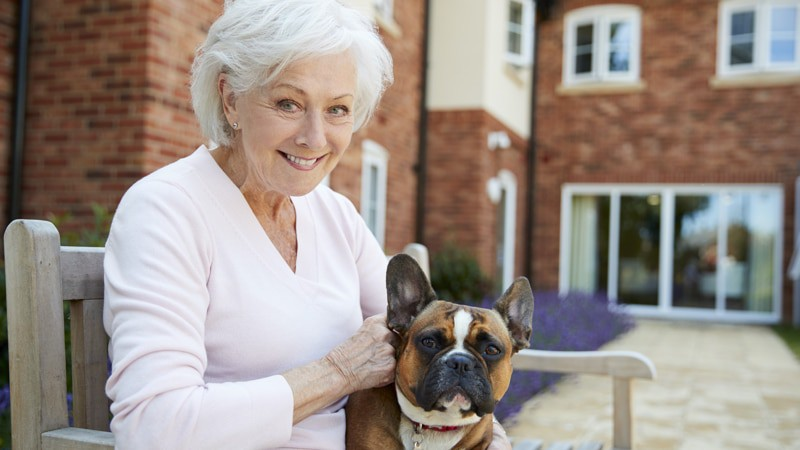 Woman at assisted living facility smiling with her dog Soup