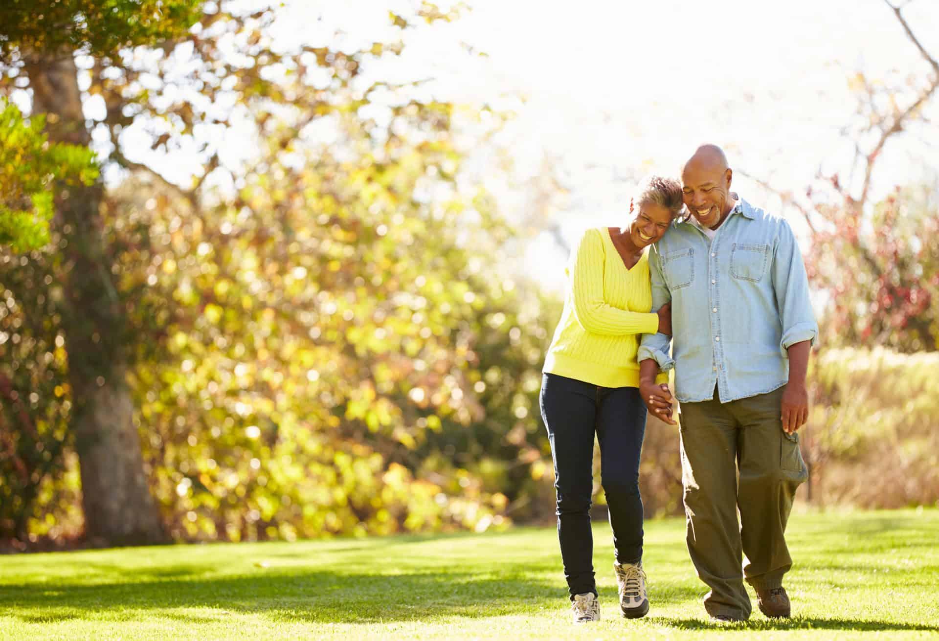 Senior couple walking through autumn woodland holding hands and smiling.