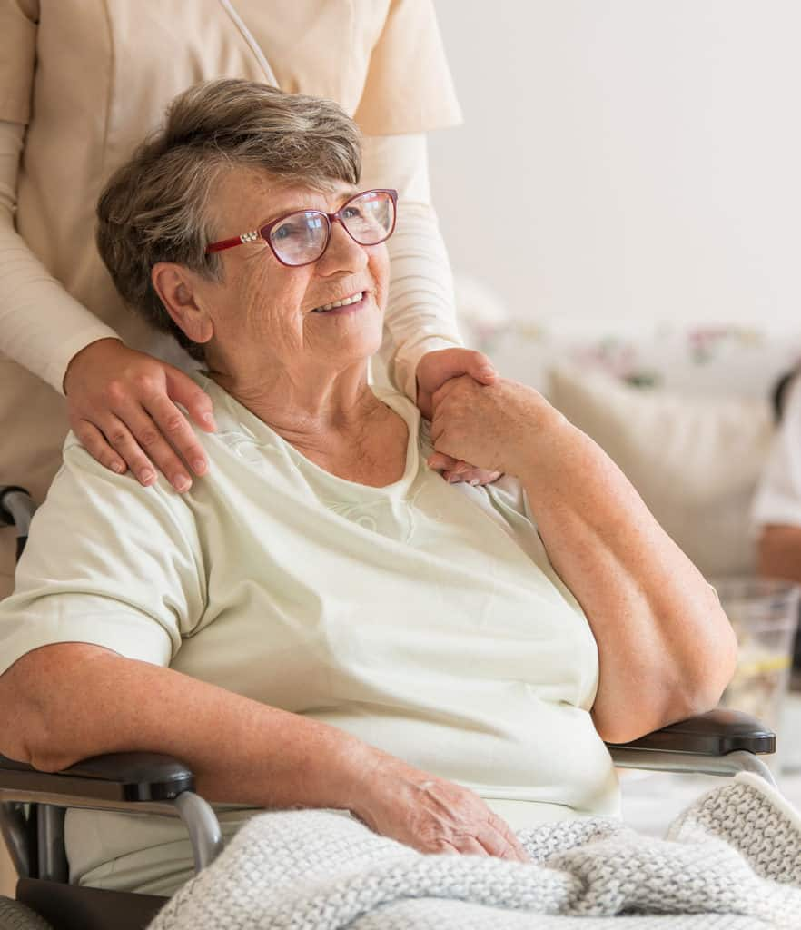 Happy senior lady sitting at wheelchair holding a caregivers hand