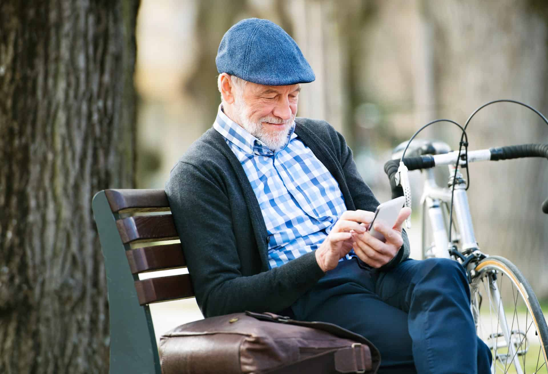 Active senior resting on park bench to check his smartphone