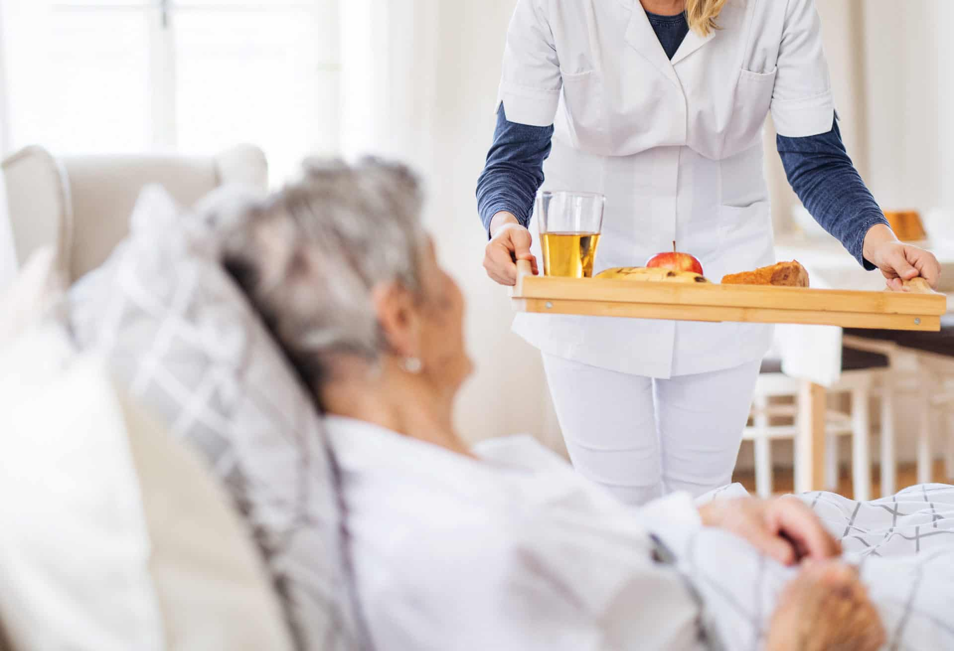 A caregiver bringing breakfast to a sick senior woman lying in bed.
