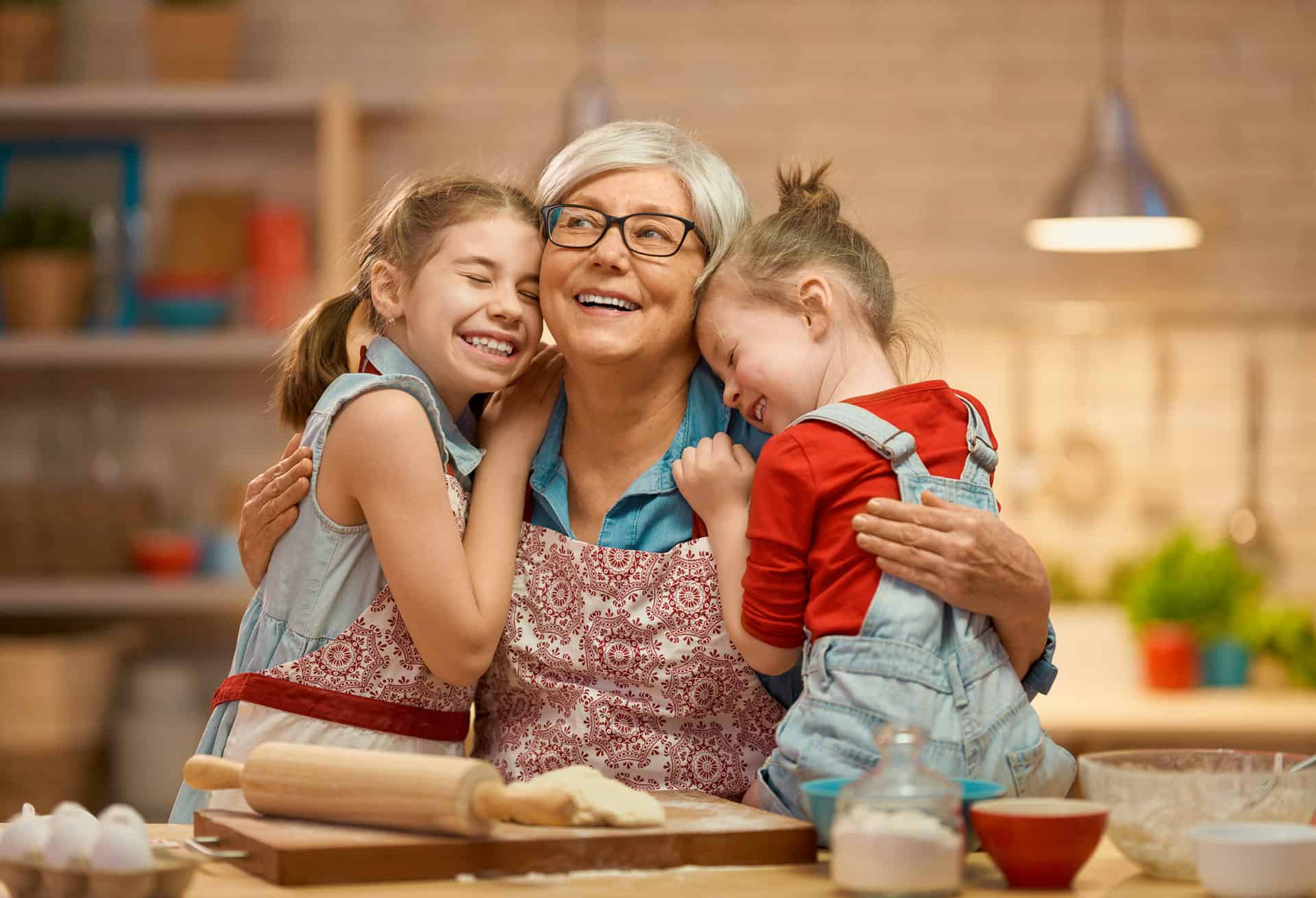 Grandmother with granddaughters baking in the kitchen hugging and smiling