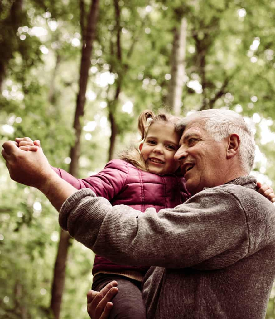 Grandpa carrying granddaughter in woods while both are smiling