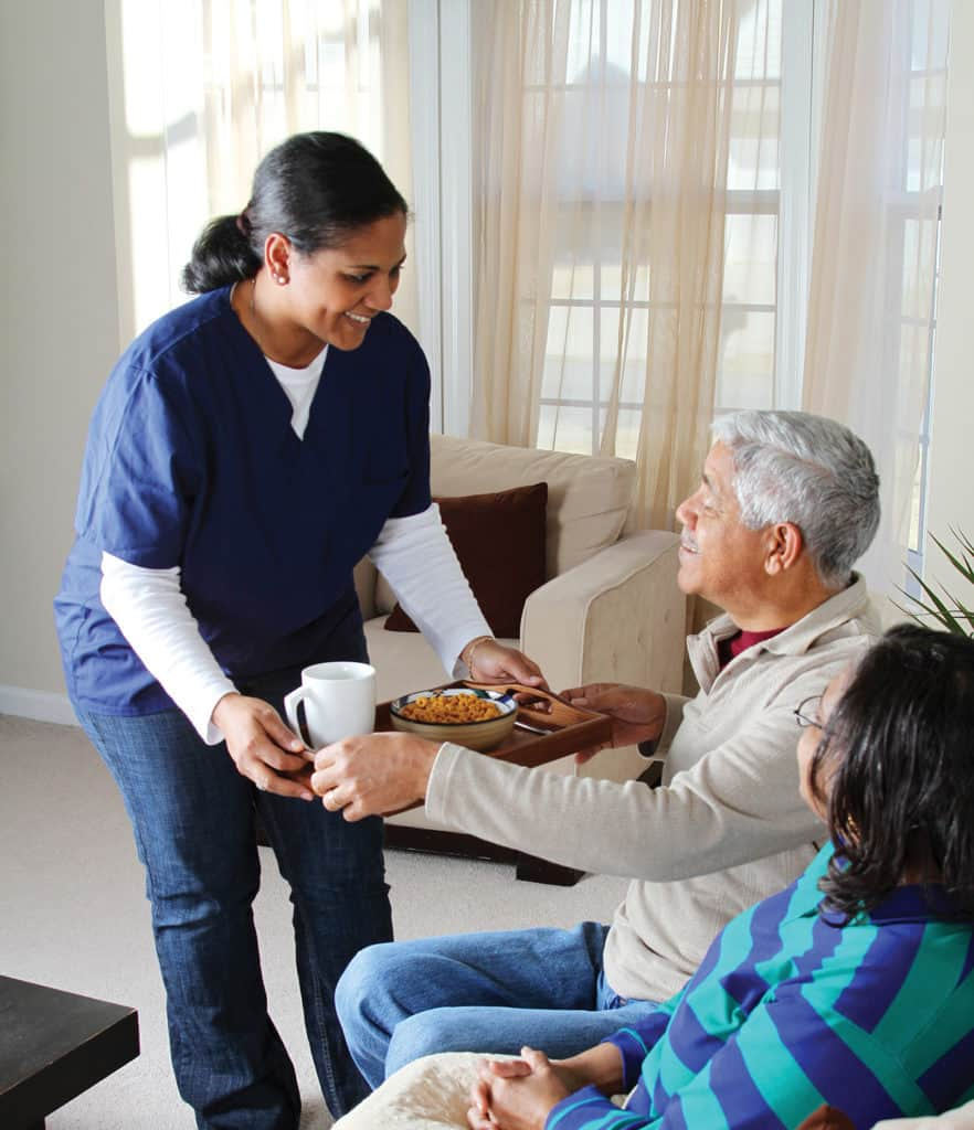 Home care worker bringing a bowl of food to senior parent.