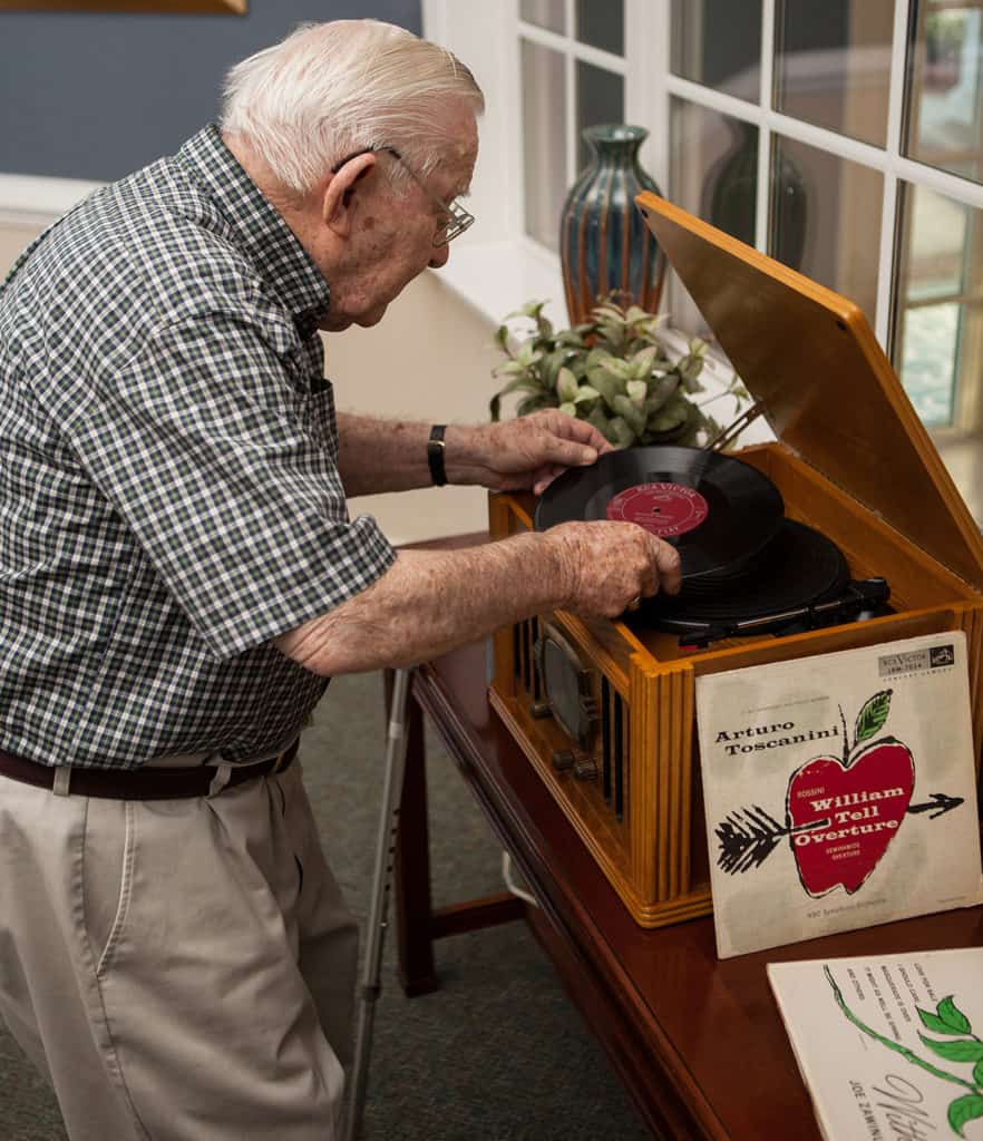 Senior man putting a record on record player.