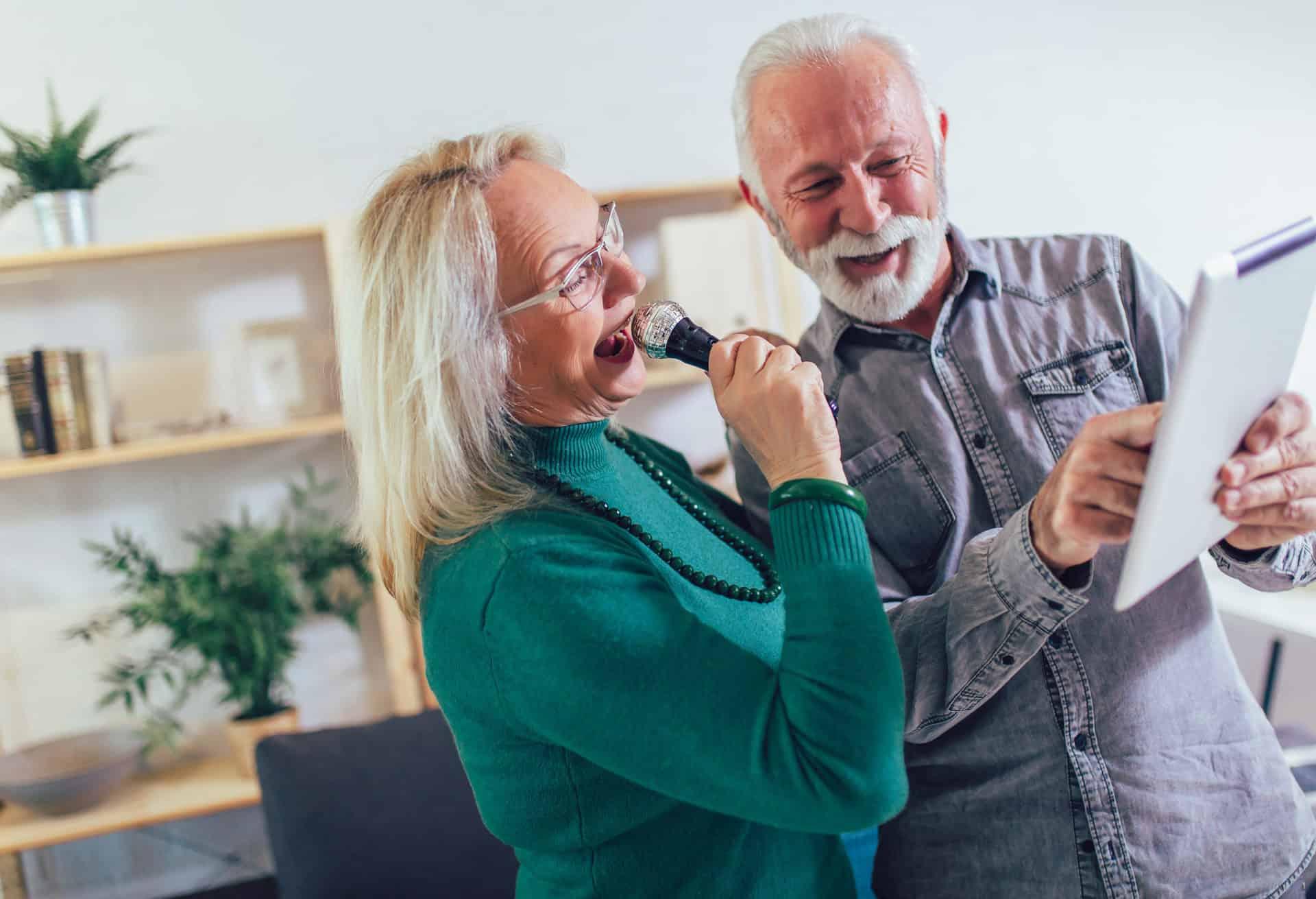 Senior couple having a good time singing karaoke together