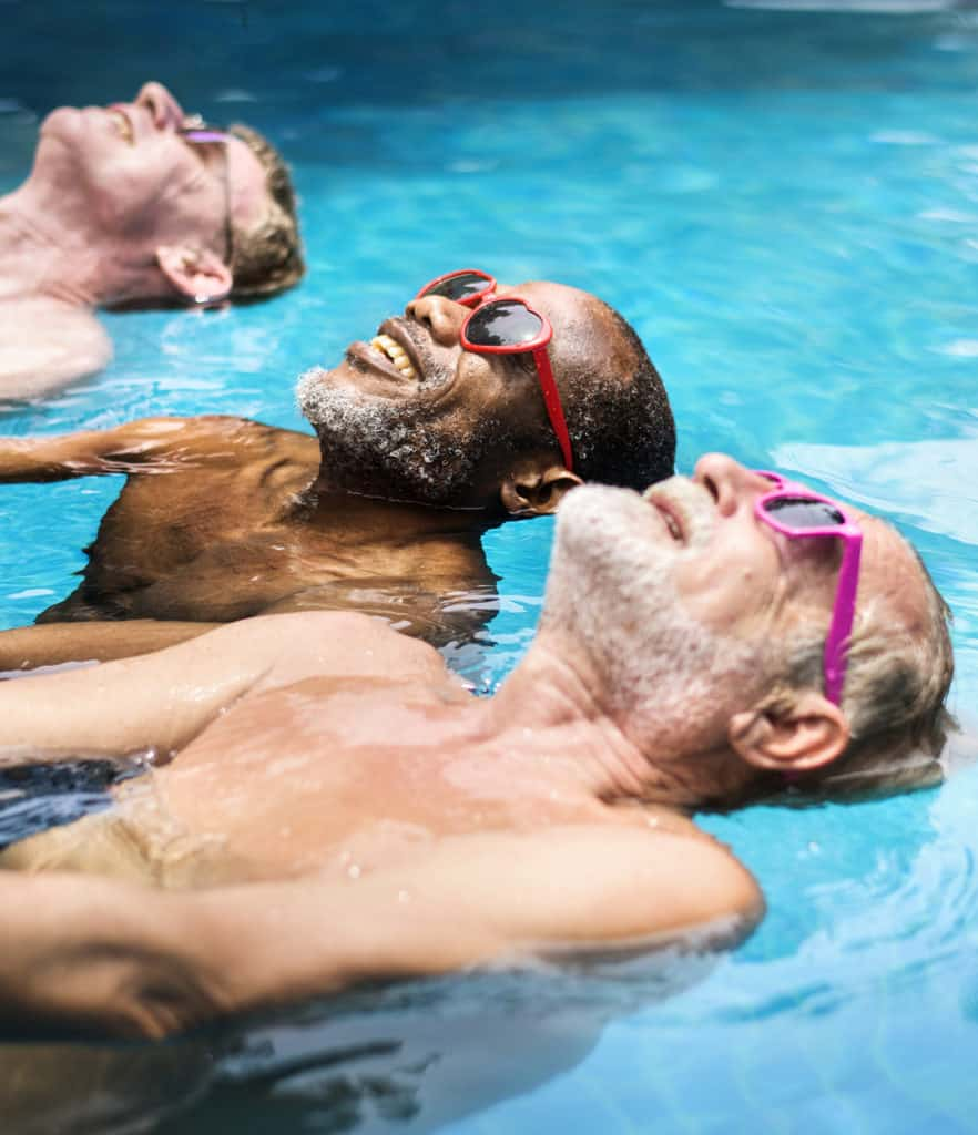 A group of senior men wearing sunglasses enjoying the pool together.