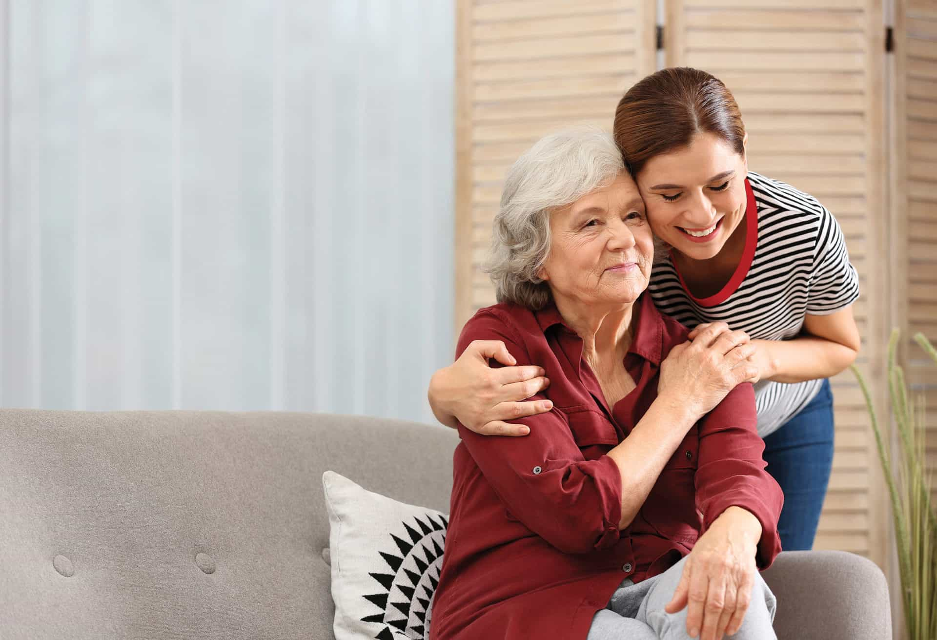 Elderly woman with female caregiver hugging in living room.