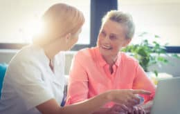 Smiling senior woman speaking with caregiver.