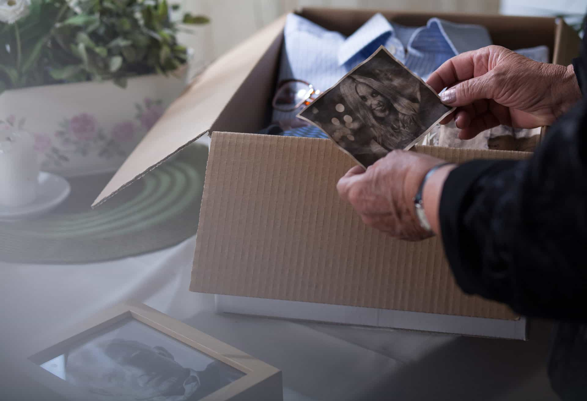 Woman packing items for donation and looking at an old picture