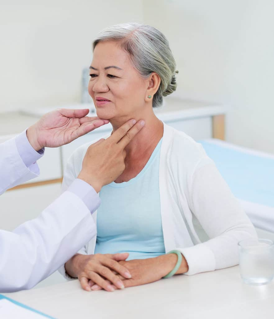 Woman receiving throat examination by a doctor