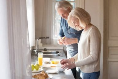 Happy senior couple make healthy breakfast on home kitchen