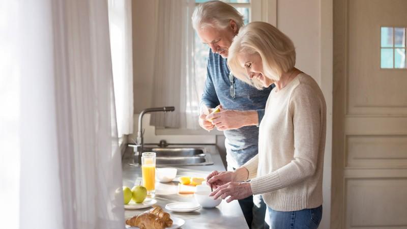 Happy senior couple make healthy breakfast on home kitchen