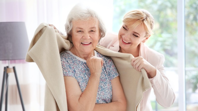 Caregiver keeping patient warm in her continuing care at-home