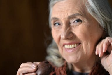 Happy senior woman eating chocolate cookie at home as a natural mood boosters