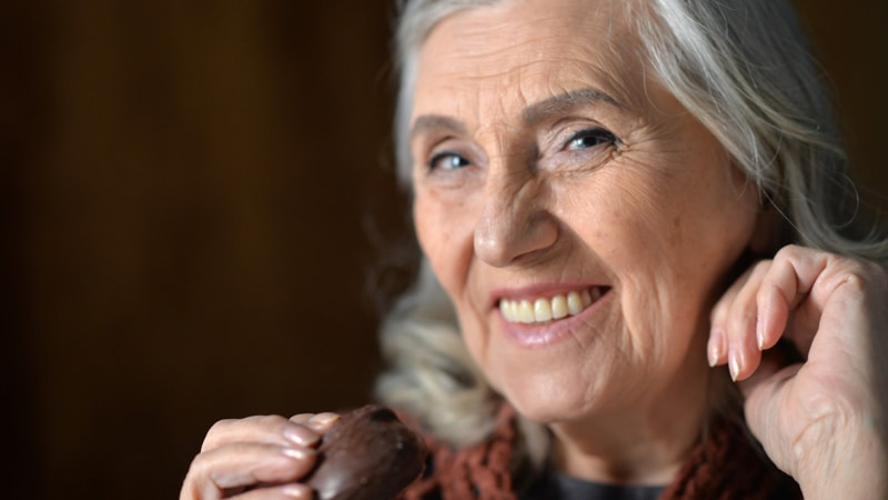 Happy senior woman eating chocolate cookie at home