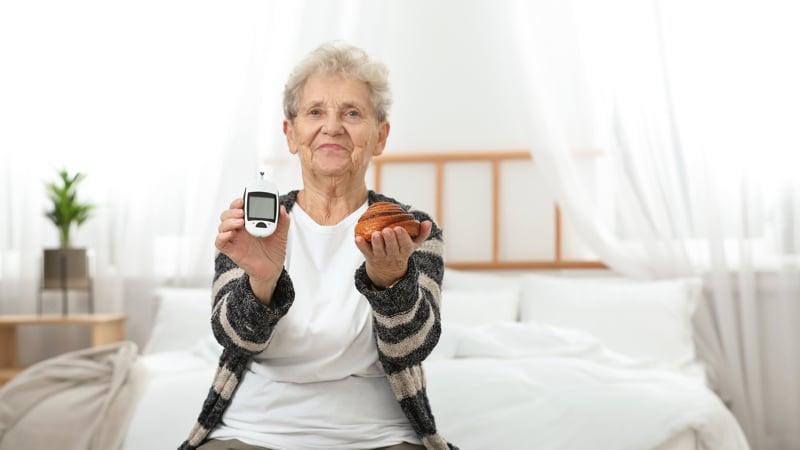Senior woman holding digital glucometer and pastry at home. Diabetes diet