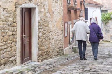A senior couple walking on the streets of an ancient city Motovun on Istria in Croatia, Europe.