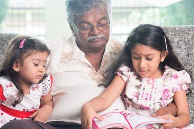 Grandparent and grandchildren reading story book.