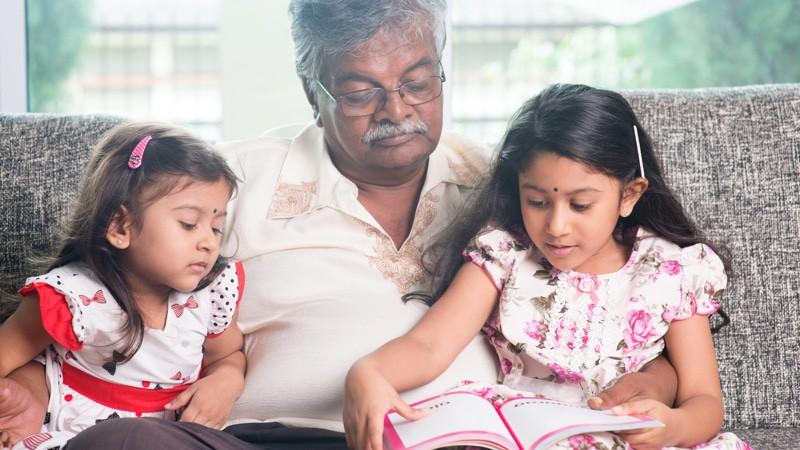 Grandparent and grandchildren reading story book.