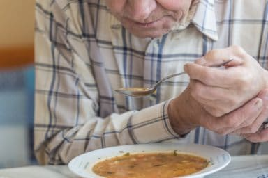 Man with Parkinson's disease tries to eat Campbell's bean soup