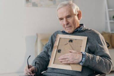 Senior thoughtful man sitting in chair and holding old photo frame from Memories in Paint