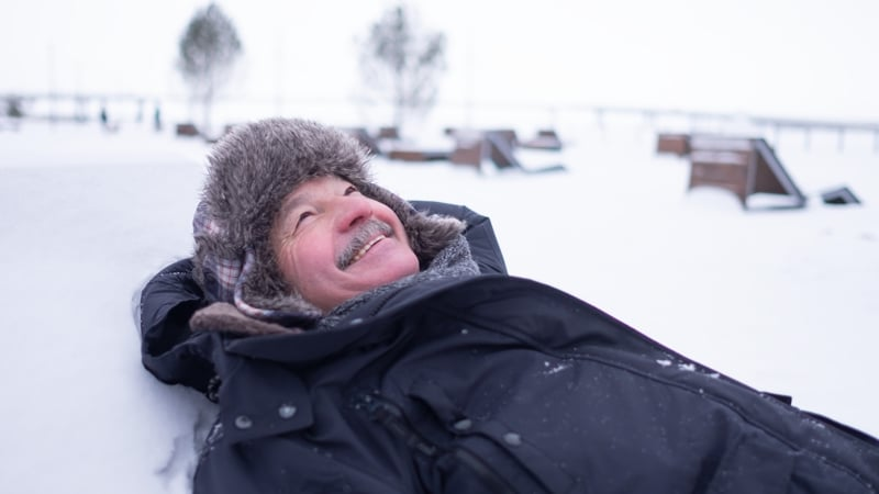 Senior handsome man in warm clothes and hat lying on snow and dreaming having fun