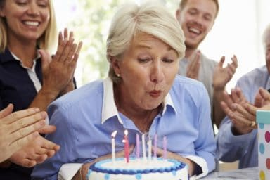 Senior Woman Blows Out Birthday Cake Candles At Family Party