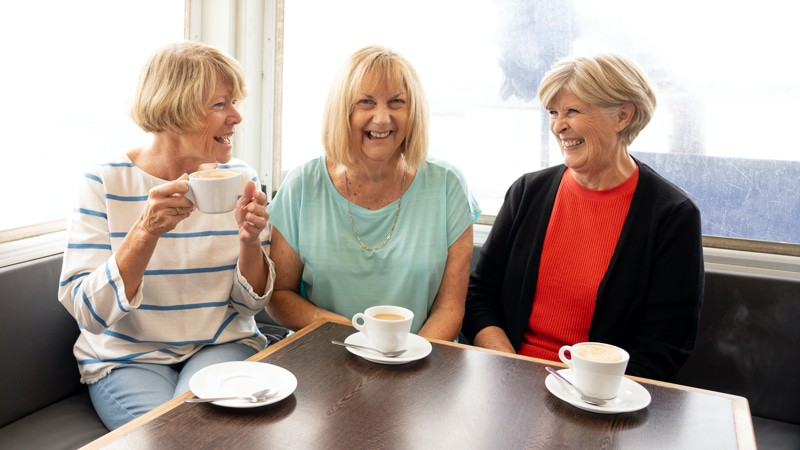 Fun older women sitting together drinking coffee and complaining about their late husbands