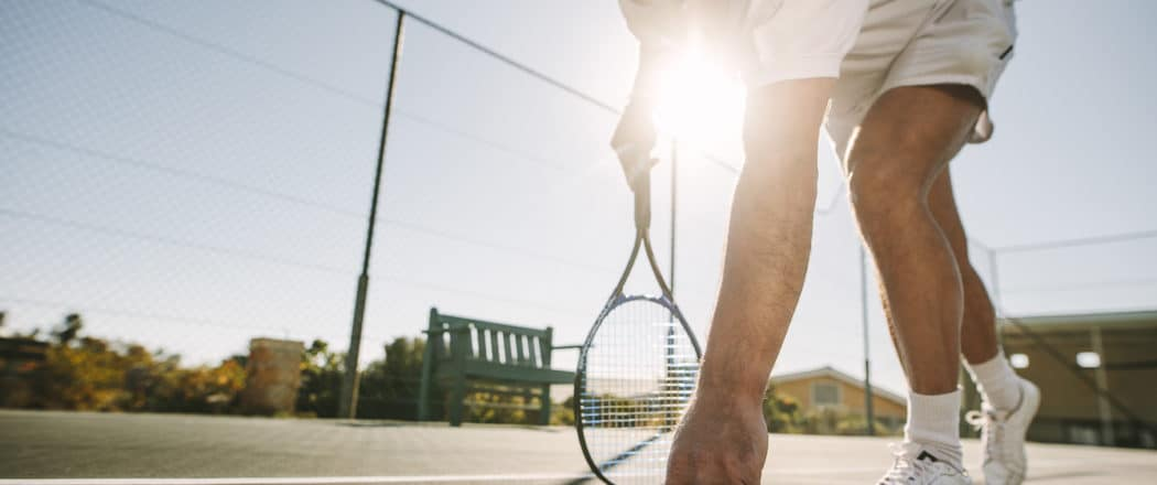 active adult playing tennis