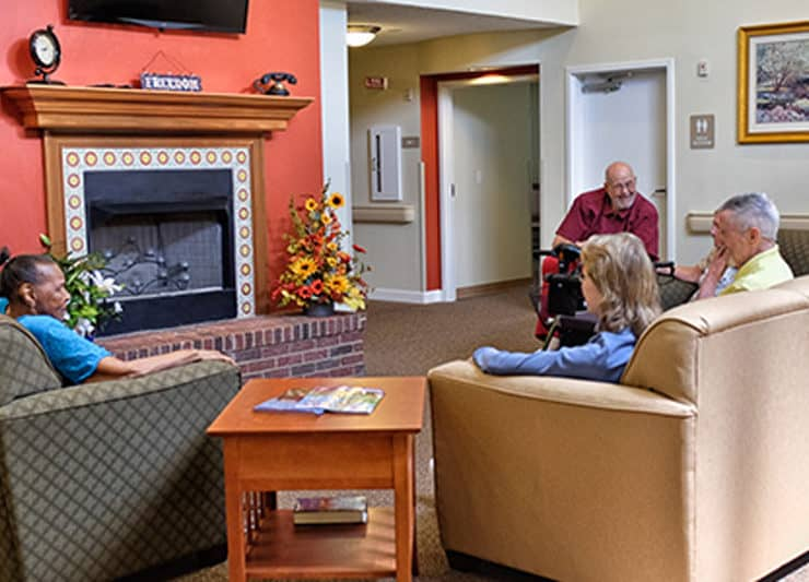 Residents of Cottages of Clayton sitting in front of Fireplace