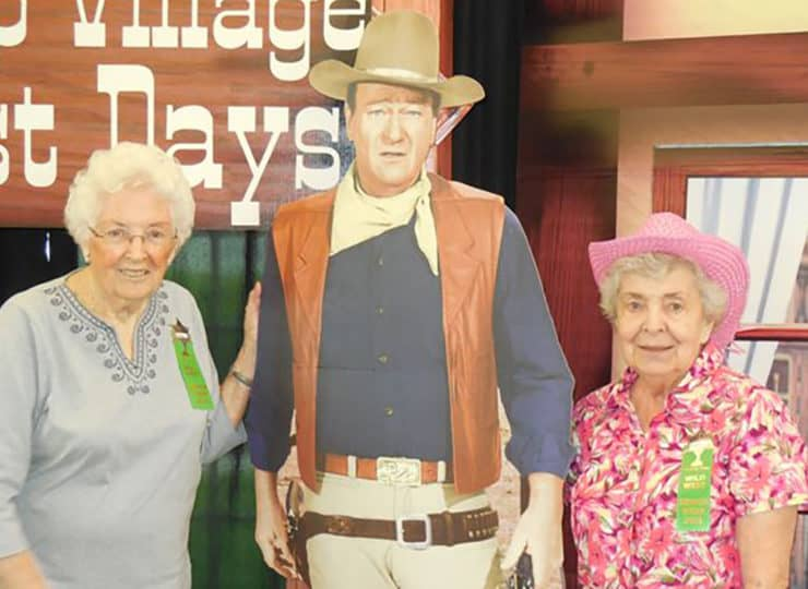 Residents pose with John Wayne cardboard display