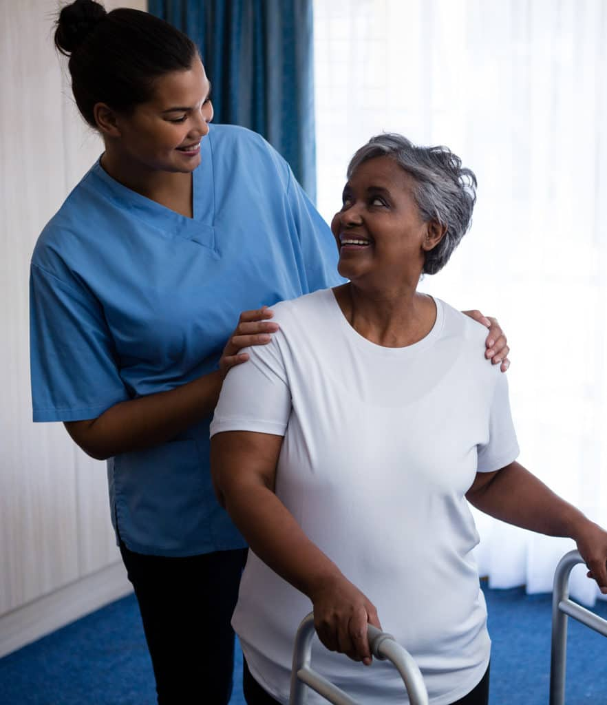 smiling caregiver helping senior woman with walker
