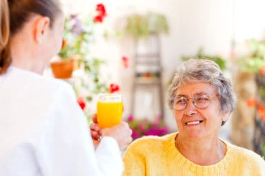 Senior drinking a mimosa during home care