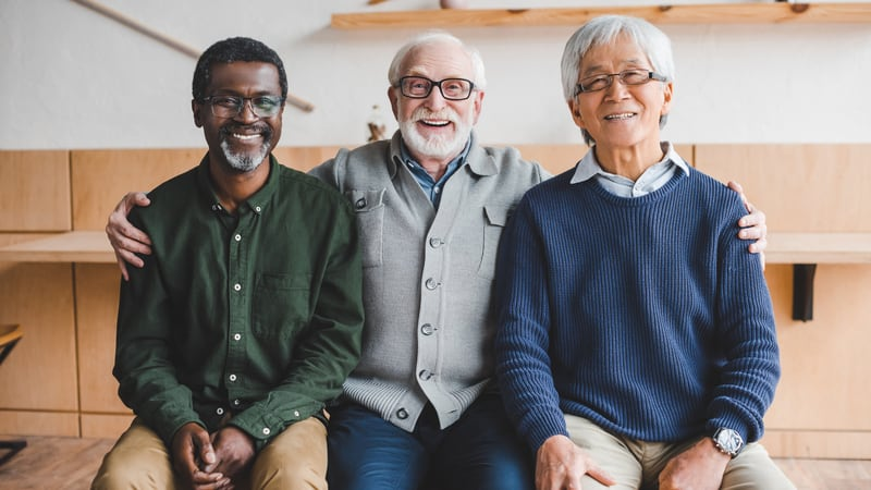 Three men celebrating their friendships at a senior living community