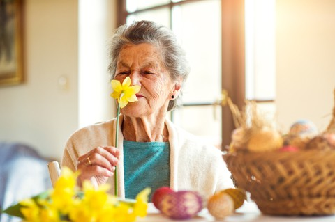 Senior woman at a memory care center smelling flowers