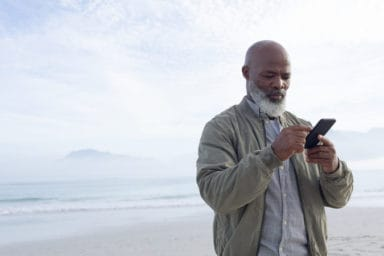 Lonely senior on the beach looks up apps for loneliness