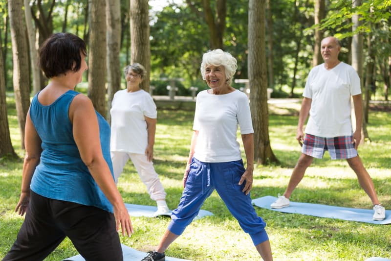 Residents at assisted living stay social with outdoor yoga