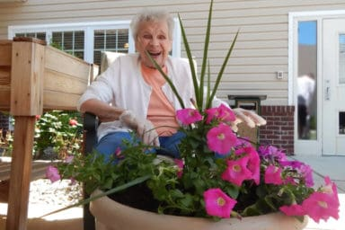 happy senior woman and potted flowers