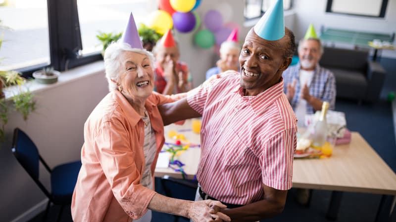 Active adult living seniors dancing together at a birthday party