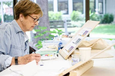Senior woman at Baker Hunt Art and Cultural Center painting