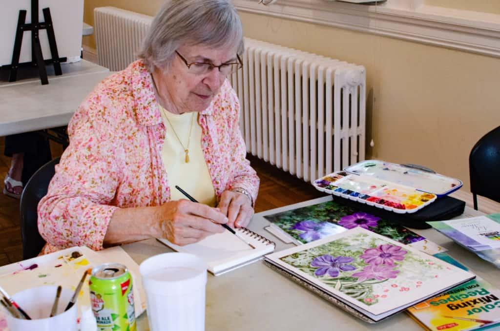 Senior woman using watercolors at Baker Hunt Art and Cultural Center