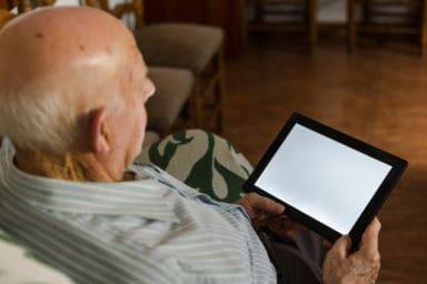 Senior man using assistive technology for seniors