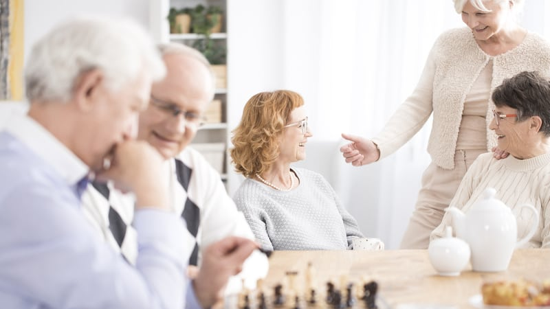 Seniors playing chess in their congregate housing for seniors