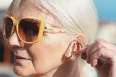 Senior woman using hearing aid trends